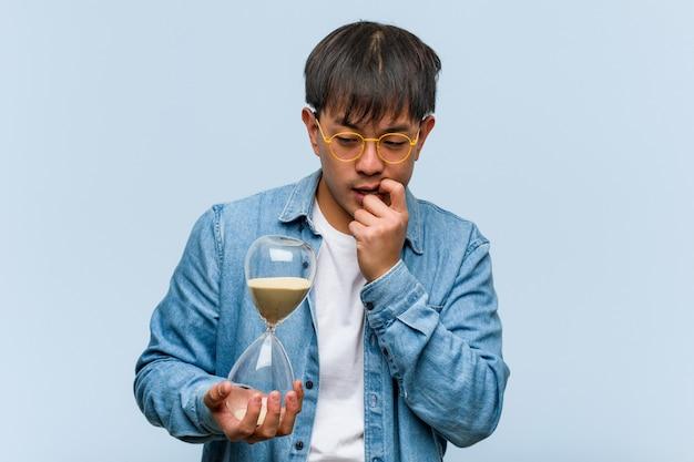 Il giovane uomo cinese che tiene un temporizzatore della sabbia si è disteso pensando a qualcosa alla a