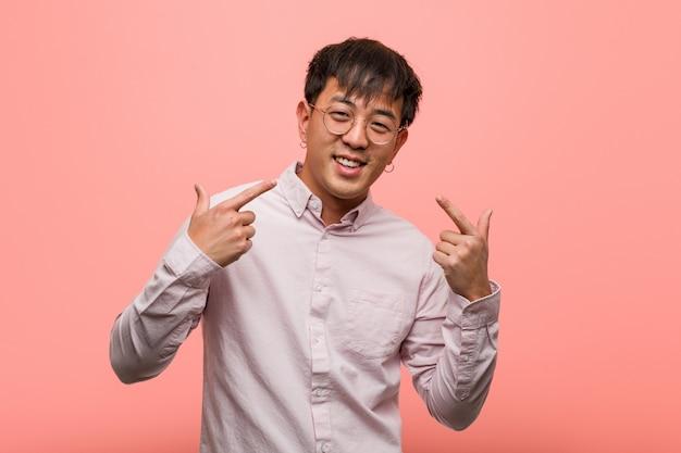 Il giovane uomo cinese sorride e si indica