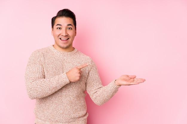 Il giovane uomo curvy che posa in una parete rosa ha isolato eccitato tenendo uno spazio della copia sul palmo.