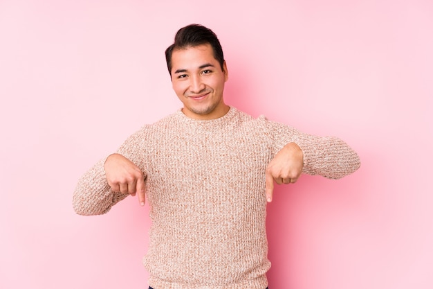 Il giovane uomo curvy che posa in una parete rosa ha isolato i punti giù con le dita, la sensibilità positiva.