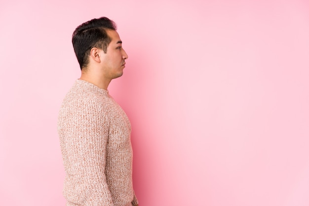 Il giovane uomo curvy che posa in una parete rosa ha isolato lo sguardo a sinistra, posa laterale.