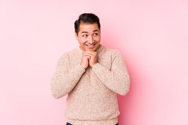 Il giovane uomo curvy che posa in una parete rosa isolata tiene le mani sotto il mento, sta guardando felicemente da parte.