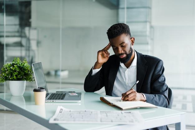 Il giovane uomo d'affari africano che lavora nell'ufficio al computer portatile e nota in taccuino