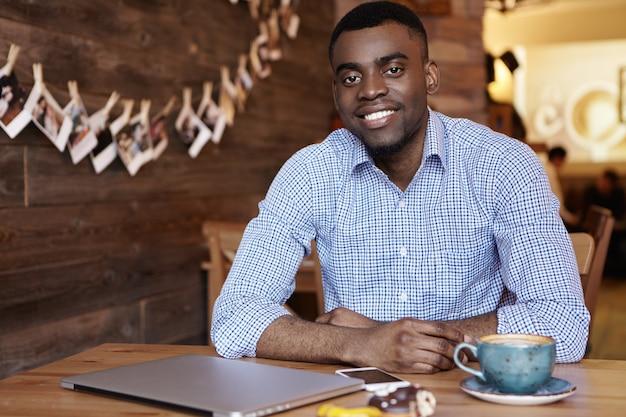 Il giovane uomo d'affari afroamericano bello felice si è vestito in camicia