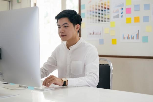 Il giovane uomo d'affari analizza il marketing online nel suo computer