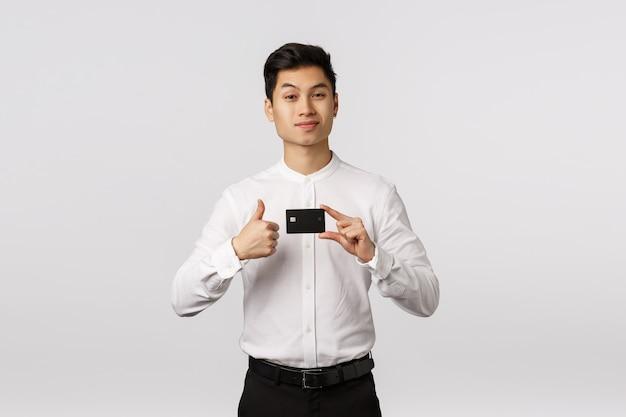 Il giovane uomo d'affari asiatico assertivo bello raccomanda la banca, tenendo la carta di credito fa il pollice in su, sorride e alza un sopracciglio con espressione orgogliosa e soddisfatta