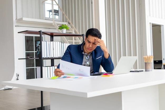 Il giovane uomo d'affari asiatico esamina i cattivi risultati finanziari dell'azienda.