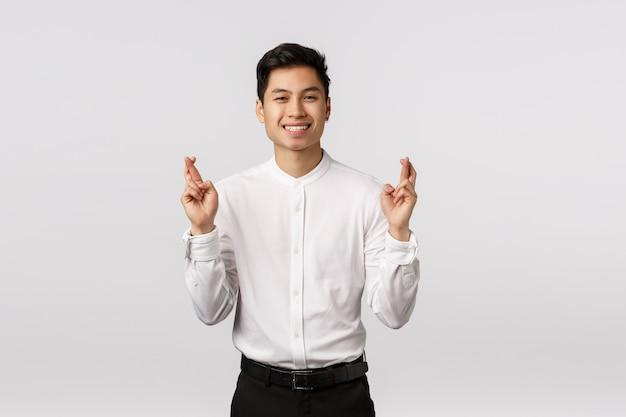 Il giovane uomo d'affari asiatico fiducioso, fortunato e ottimista ha fiducia che tutto vada bene, incrocia le dita buona fortuna, assapora il risultato positivo, sorride soddisfatto, spera, prega per raggiungere l'obiettivo