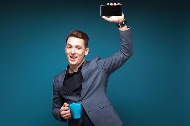 Il giovane uomo d'affari attraente in rivestimento grigio e camicia nera tiene la tazza blu e mostra il telefono