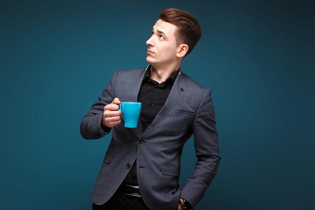 Il giovane uomo d'affari attraente in rivestimento grigio e camicia nera tiene la tazza blu
