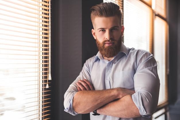 Il giovane uomo d'affari barbuto bello sta esaminando la macchina fotografica.