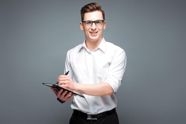 Il giovane uomo d'affari bello in orologio costoso, i vetri neri e la camicia bianca tengono la compressa e la penna