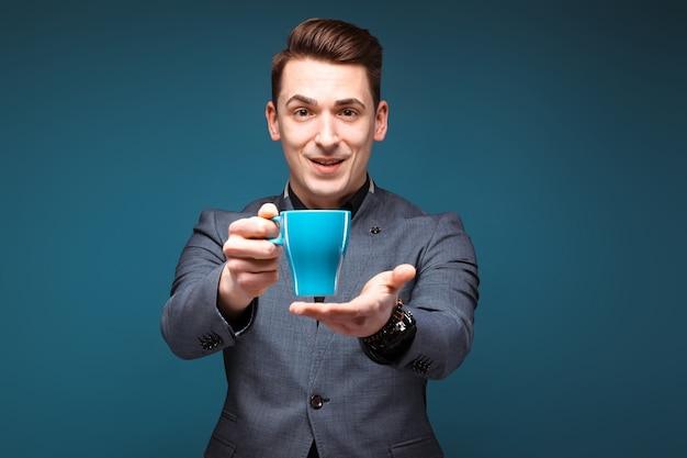 Il giovane uomo d'affari bello in rivestimento grigio e camicia nera tiene la tazza blu