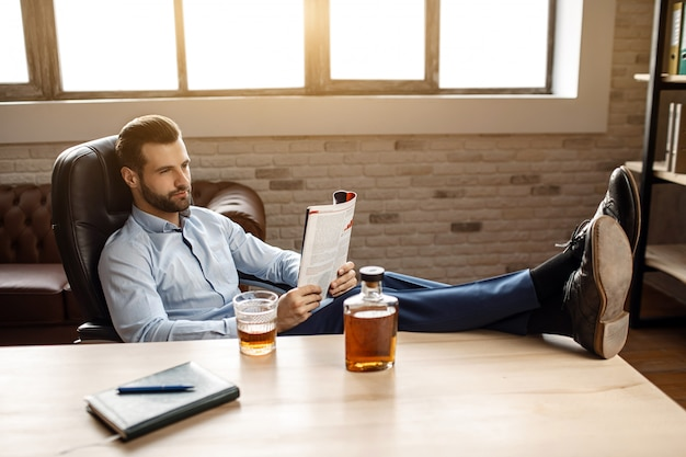Il giovane uomo d'affari bello si siede alla tavola e legge il giornale nel suo ufficio. tiene le gambe sulla scrivania. vetro e grafene con whisky stanno sul tavolo. fiducioso e simpatico.