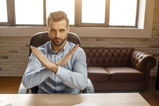 Il giovane uomo d'affari bello si siede alla tavola nel suo proprio ufficio. tiene le mani incrociate in segno proibito. arrabbiato e molto serio.