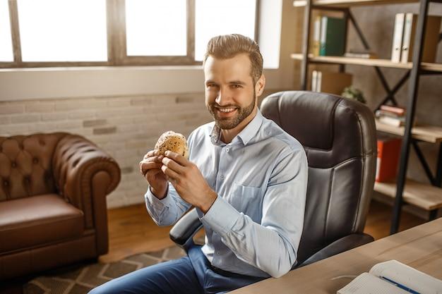 Il giovane uomo d'affari bello si siede sulla sedia e pranza l'ora nel suo ufficio. tiene un hamburger e sorride alla telecamera. giovane uomo affamato positivo che mangia.