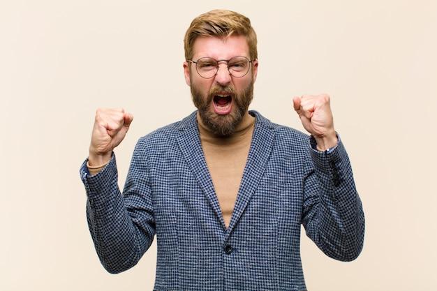 Il giovane uomo d'affari biondo che grida aggressivamente con un'espressione arrabbiata o con i pugni ha serrato la celebrazione del successo