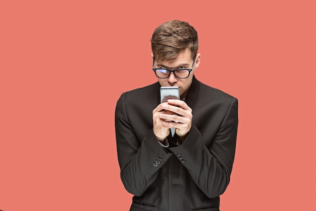 Il giovane uomo d'affari caucasico in bicchieri su sfondo rosso studio parlando al cellulare