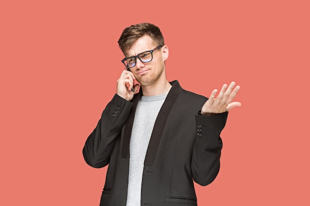 Il giovane uomo d'affari caucasico su sfondo rosso, parlando al telefono cellulare