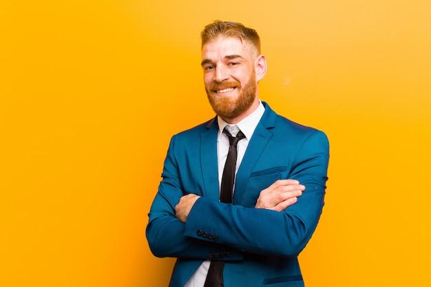 Il giovane uomo d'affari della testa rossa che assomiglia ad un realizzatore felice, fiero e soddisfatto che sorride con le armi ha attraversato contro la parete arancio