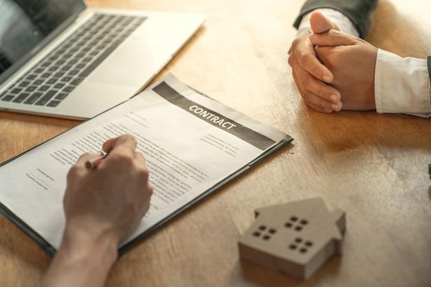 Il giovane uomo d'affari e il cliente acquirente domestico avevano raggiunto insieme i mezzi target e avevano firmato il contratto di vendita di immobili