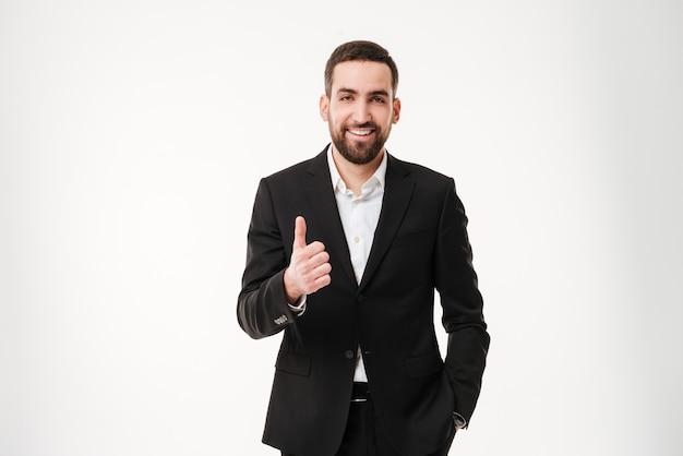 Il giovane uomo d'affari felice che mostra i pollici aumenta il gesto.