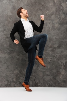 Il giovane uomo d'affari felice fa il gesto del vincitore.