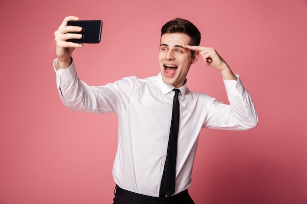 Il giovane uomo d'affari felice fa il selfie dal telefono cellulare.