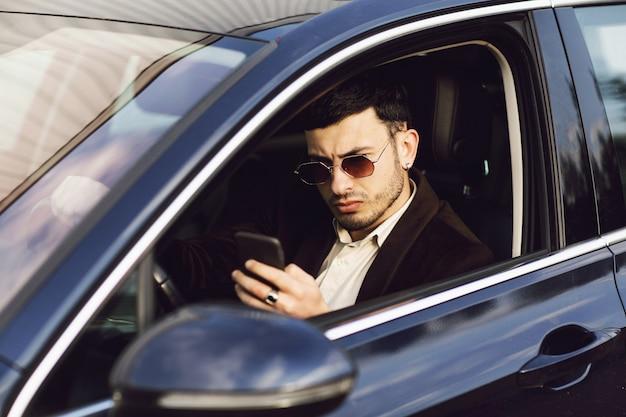Il giovane uomo d'affari in tuta e occhiali neri parla al telefono nella sua auto. aspetto d'affari. test drive della nuova auto