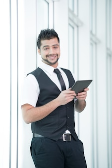 Il giovane uomo d'affari indiano sta tenendo una compressa in mani.