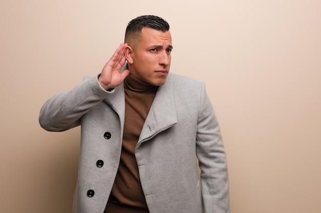Il giovane uomo d'affari latino prova ad ascoltare un gossip
