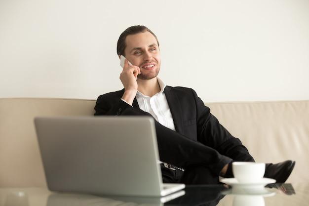 Il giovane uomo d'affari lavora a distanza dalla camera d'albergo