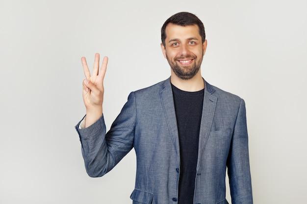Il giovane uomo d'affari maschio con la barba che sorride mostrando le dita numera tre