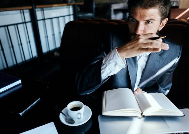Il giovane uomo d'affari maschio si siede a un tavolo con documenti e beve il caffè, guarda fuori dalla finestra