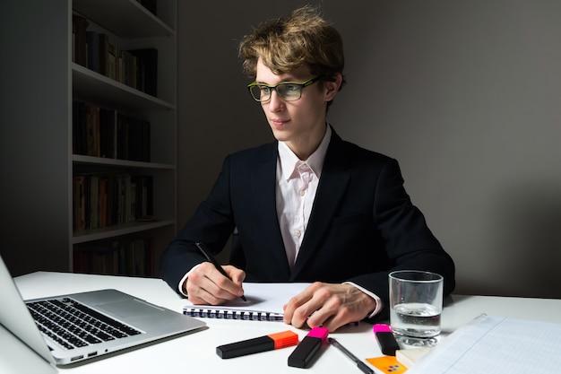 Il giovane uomo d'affari risoluto e sicuro lavora le ore tarde in ufficio sul progetto per rispettare la scadenza