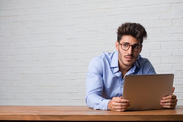 Il giovane uomo d'affari seduto e lavora su un laptop preoccupato e sopraffatto, smemorato, realizza qualcosa, espressione di shock per aver commesso un errore