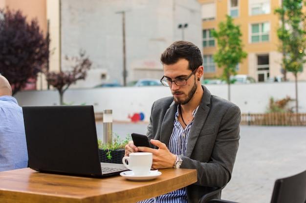Il giovane uomo d'affari sta lavorando in un bar con terrazza con il suo laptop e smartphone