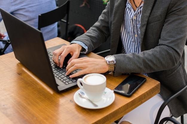 Il giovane uomo d'affari sta lavorando in una terrazza bar con il suo laptop e smartphone. avvicinamento