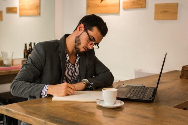 Il giovane uomo d'affari sta scrivendo in suo taccuino in un pub