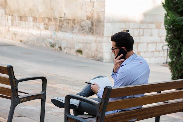 Il giovane uomo d'affari sta sedendosi su una panchina mentre sta parlando sul cellulare e sta scrivendo sul suo taccuino
