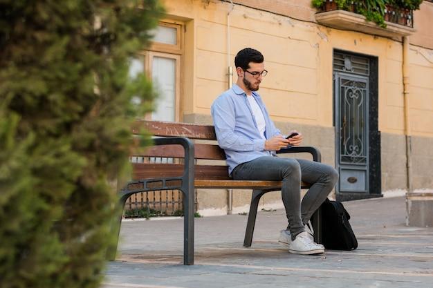 Il giovane uomo d'affari sta sedendosi su una panchina mentre sta parlando sul cellulare