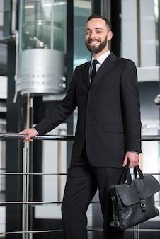 Il giovane uomo d'affari sta tenendo una valigetta.