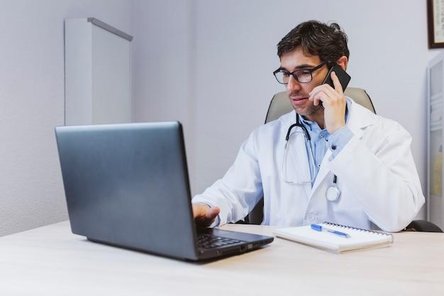 Il giovane uomo del medico che lavora al computer portatile al consulta. parlando sul cellulare. concetto medico moderno al chiuso
