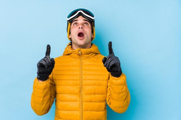 Il giovane uomo dello sciatore che indossa gli occhiali di protezione dello snowboard ha isolato indicare la parte superiore con la bocca aperta.