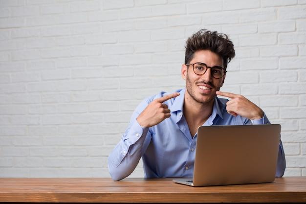 Il giovane uomo di affari che si siede e che lavora ad un sorriso del computer portatile, indicando la bocca, concetto dei denti perfetti, denti bianchi, ha un atteggiamento allegro e gioviale