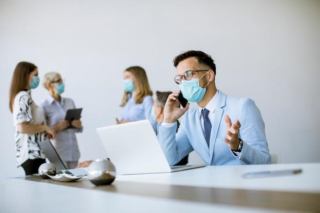Il giovane uomo di affari con la mascherina protettiva medica lavora ad un computer portatile e usando il telefono cellulare nell'ufficio