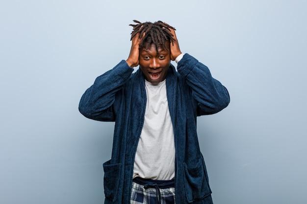 Il giovane uomo di colore africano che porta il pigiama ride con gioia tenendo le mani sulla testa. concetto di felicità.