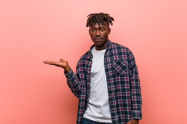 Il giovane uomo di colore africano ha colpito lo spazio della copia della tenuta sulla palma.