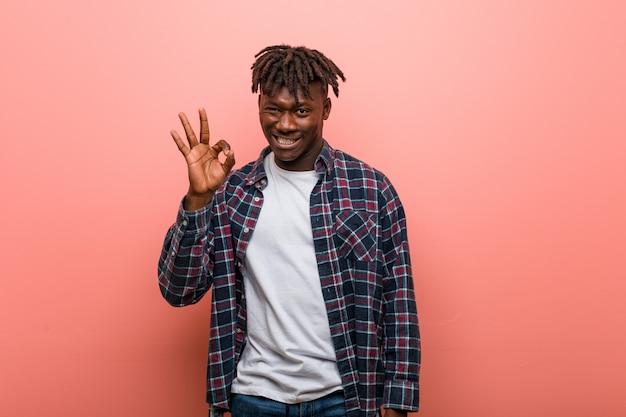 Il giovane uomo di colore africano strizza l'occhio e tiene un gesto giusto con la mano.