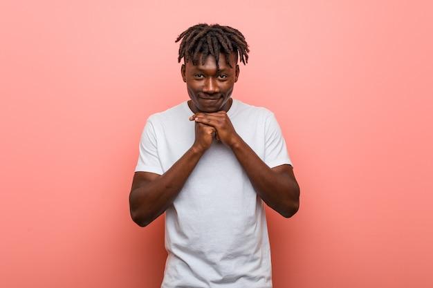 Il giovane uomo di colore africano tiene le mani sotto il mento, sta guardando felicemente da parte.